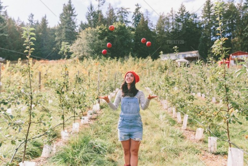 a woman juggling fruit